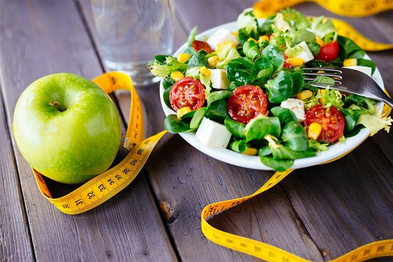 Un bol de salade grecque, une pomme et un ruban de mesure.