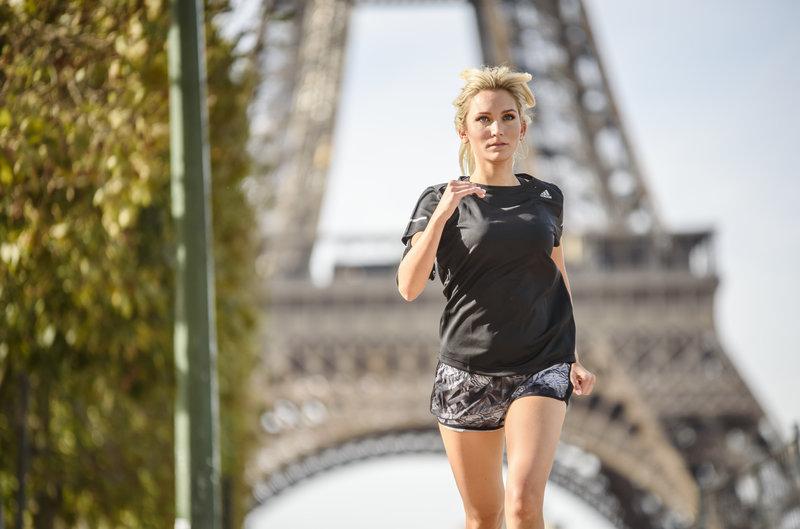 Jeune femme courant devant la tour Eiffel