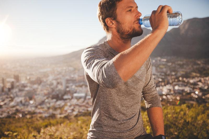 Ein Mann macht eine Pause und trinkt Wasser aus einer Flasche