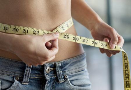 Eine schlanke Frau kontrolliert ihren Taillenumfang mit einem Messband