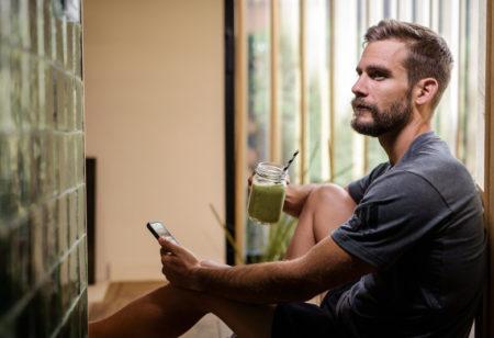 Ein Mann sitzt nach dem Sport in der Küche und trinkt einen grünen Smoothie