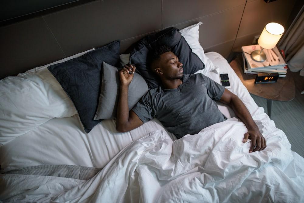 Mann schläft in seinem Bett ein