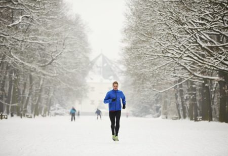 Young runner in winter jogging in park.