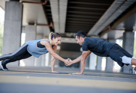 A woman and a man doing a partner workout outside