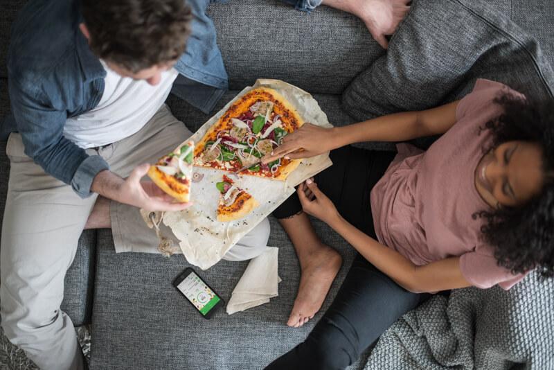 Eine Mann und eine Frau essen Pizza auf der Couch