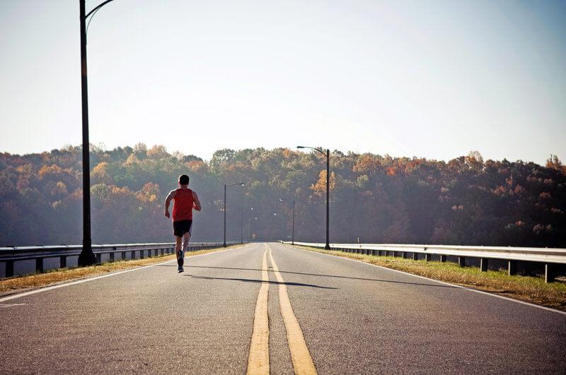 Mann laeuft eine Strasse entlang.