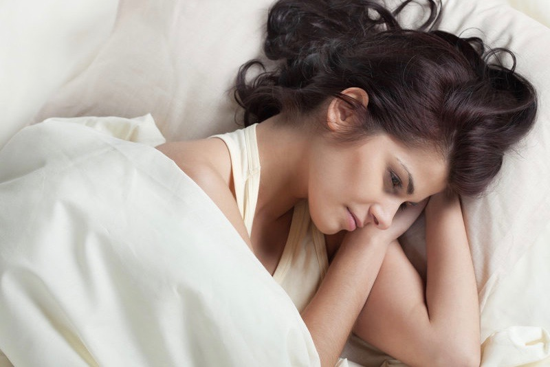 Young woman is lying awake in bed