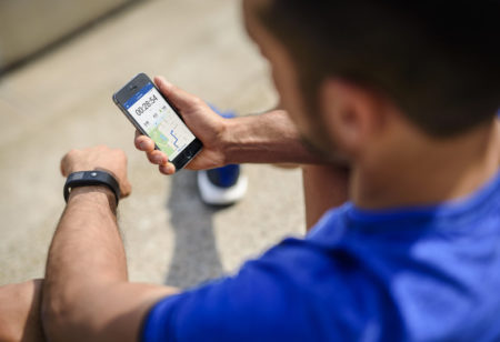 Young man checking his training session on his smartphone.