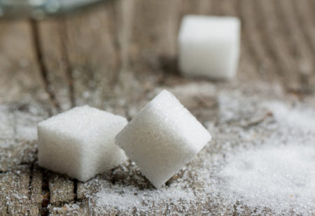 Zuckerwuerfel auf einem Holztisch.