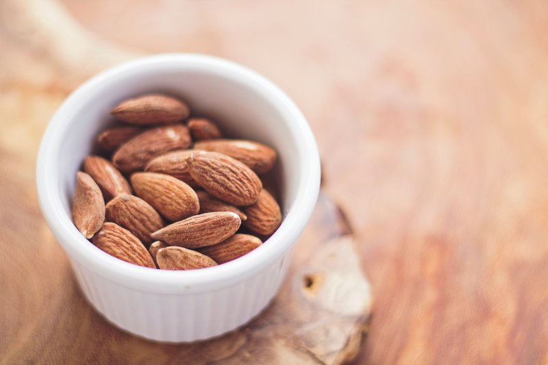 A bowl full of almonds on a wooden table
