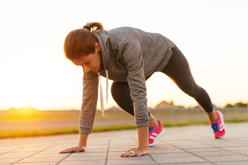 Image of attractive female in sports clothing, jogging in urban part of city, near the road in sunset in summer. Location: Central Europe