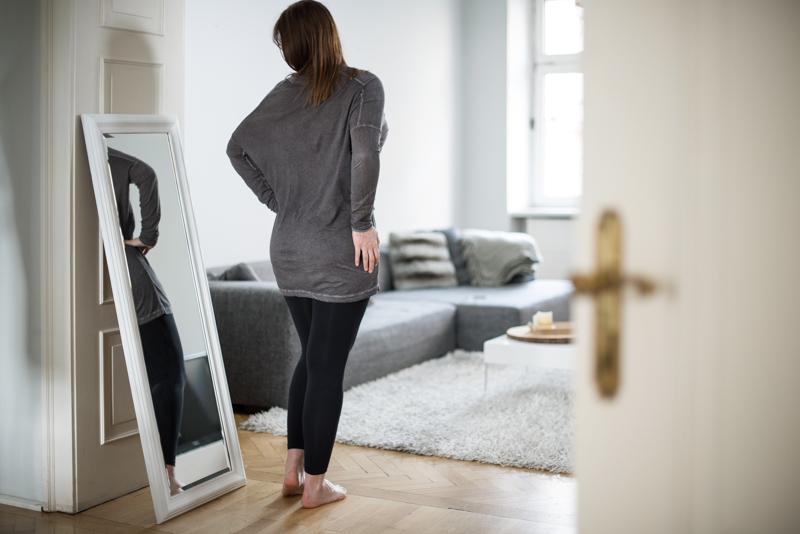 Eine Frau betrachtet sich im Spiegel