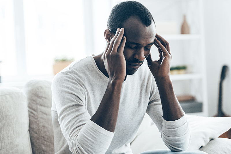 Ein Mann sitzt am Schreibtisch und greift sich vor Müdigkeit auf den Kopf