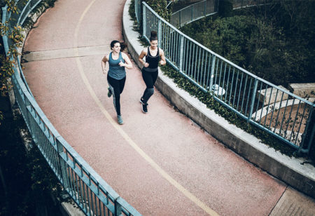couple running on a bridge.