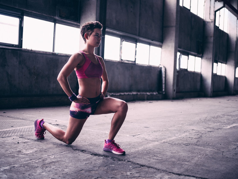 Fit teen girl wearing pink sportswear in a grey gym space warming up for exercise by performing a lunge.