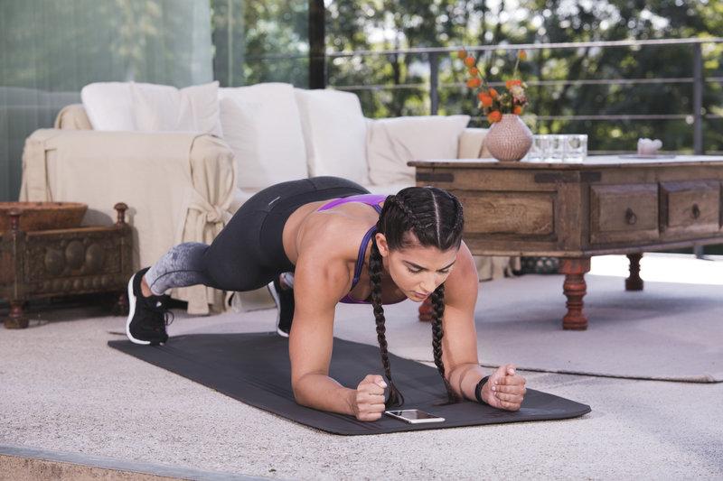 Jeune femme atlétique en position de planche dans son salon.