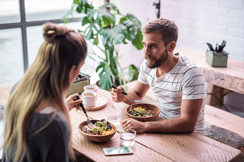 Man and woman sit together and eat