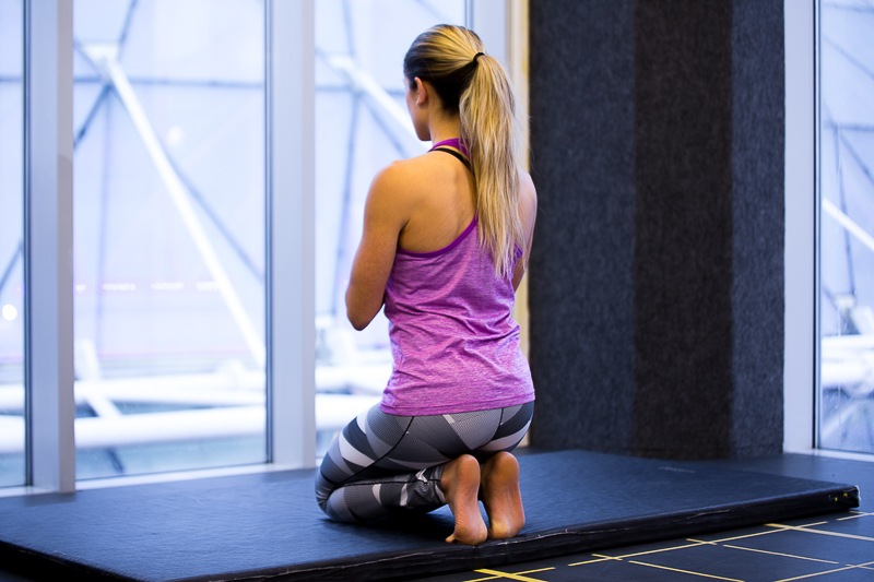 A woman is stretching in the gym