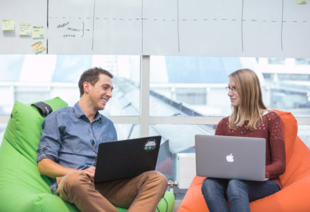 Two people sitting in beanbags with their laptops talking