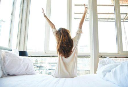 Frau wacht auf ihrem Bett auf