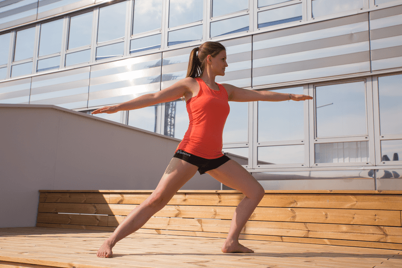 Young woman is doing yoga on the terrace
