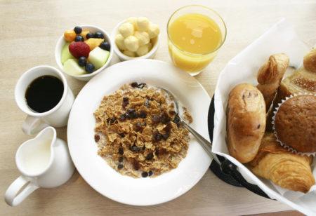Großes Frühstück mit Cornflakes, Croissants, Obst, Kaffee und Orangensaft