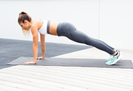 Woman is doing a plank to down dog
