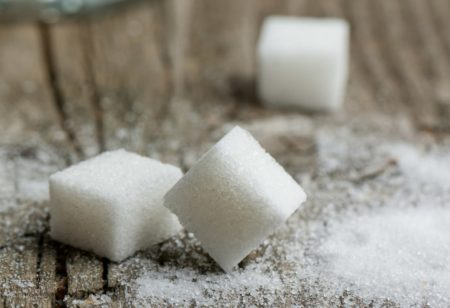 Three pieces of sugar on a wooden table.