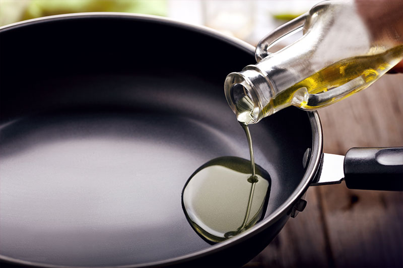 Someone pouring oil in a pan
