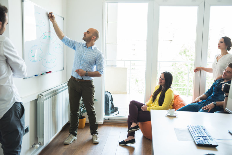 Businesspeople having a meeting in front on a whiteboard.