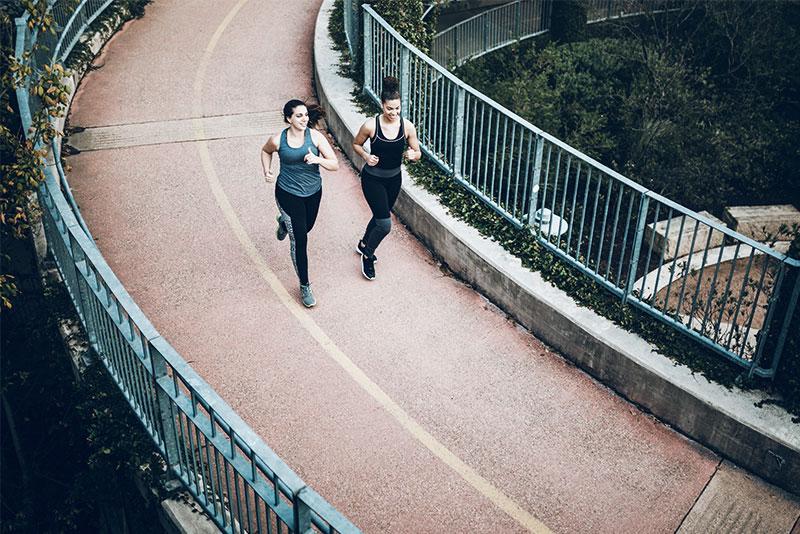 couple running on a bridge.