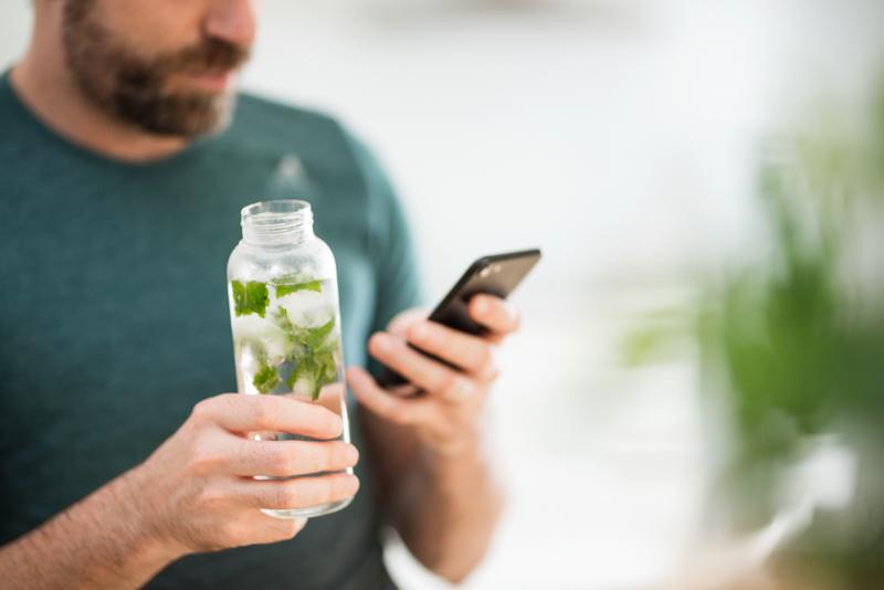 Ein Mann trinkt Wasser mit Minze aus einer Flasche