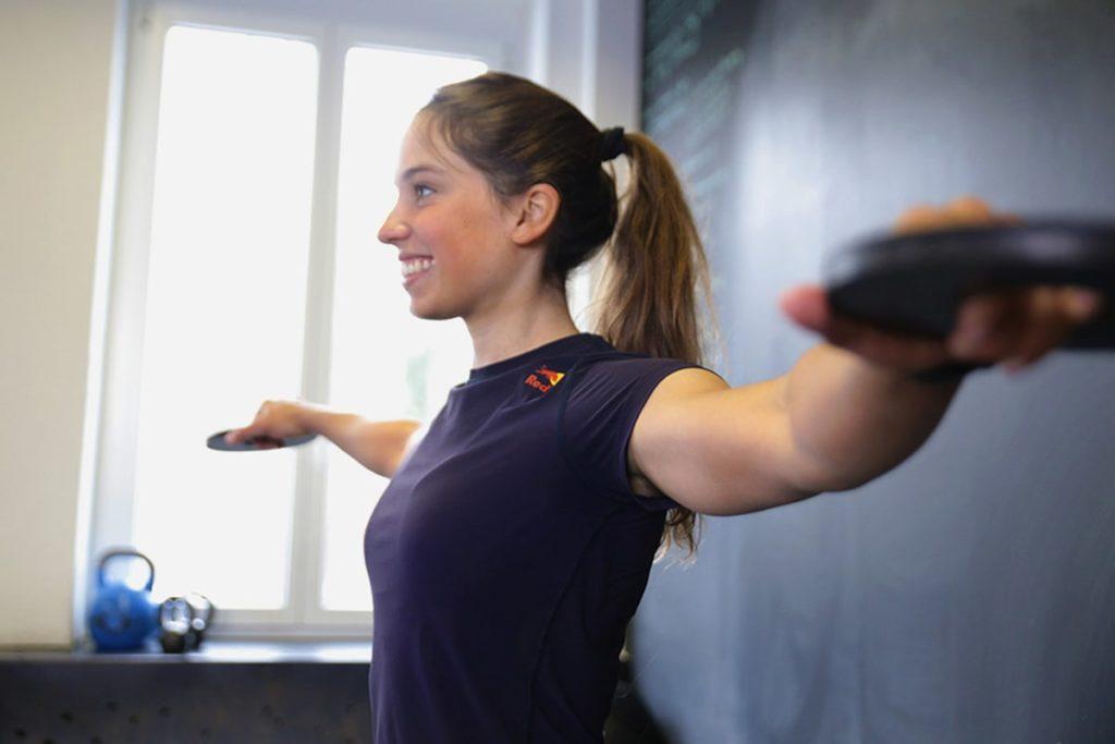 Frau macht Schulter Übung im Fitnessstudio