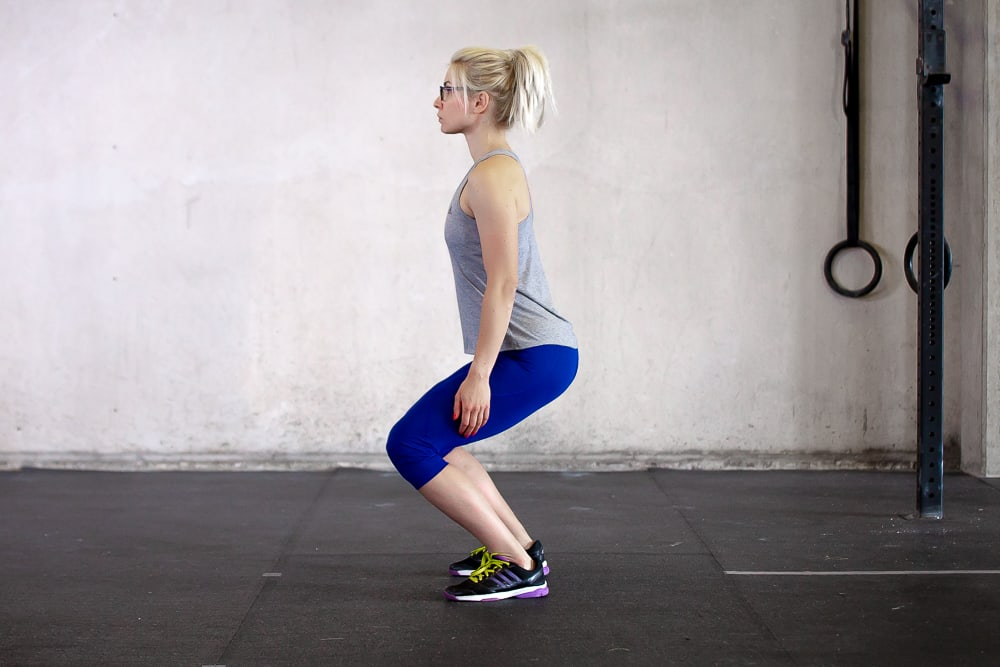 woman doing squat wrong by bending at the knees first