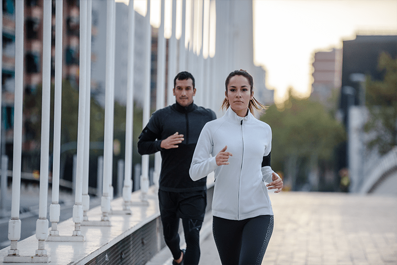 A woman and a man running outside