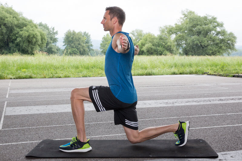 Athletic man is doing a lung forward while his upper body is rotating.