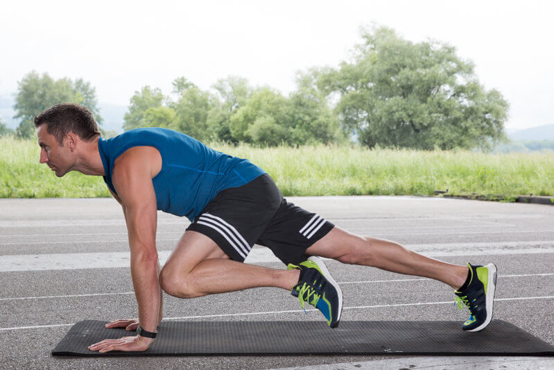 Athletic man makes a high plank while lifting his knee to the front and to the side .