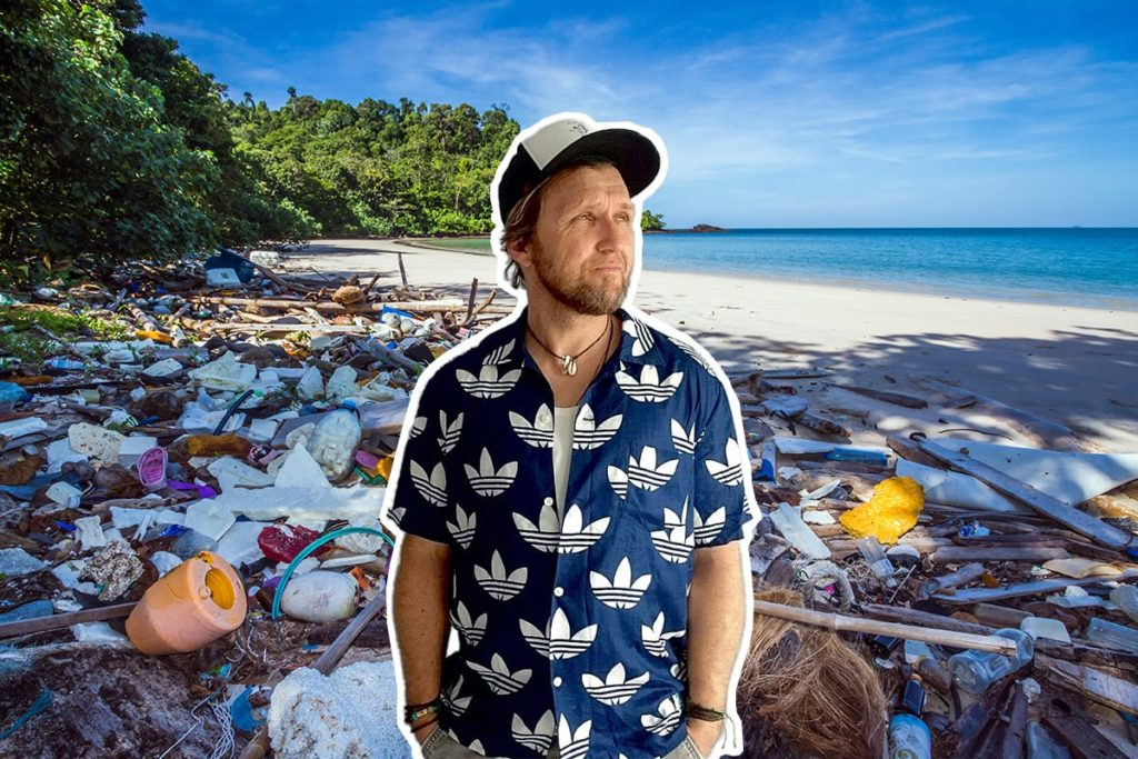 Man standing by the ocean with a lot of plastic waste on the beach behind him