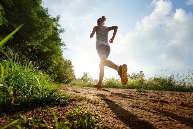 Junge Frau laeuft auf einem Feldweg.