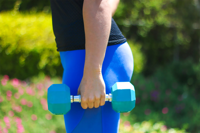 Close up of woman holding a dumbbell.