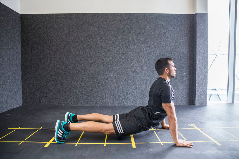 Young man who is doing an Inchworm exercise