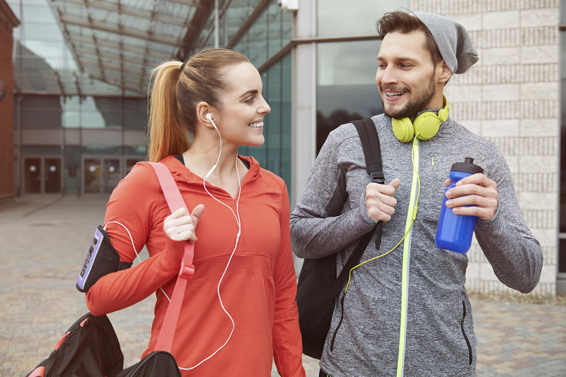 Young couple leaving the gym after their workout.