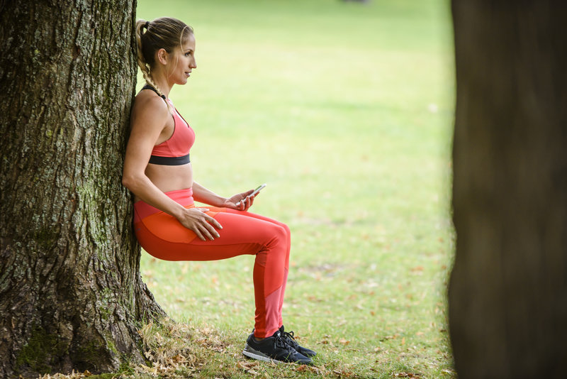 Young woman doing a bodyweight training with Runtastic Results outside.