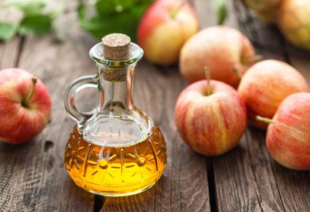 Ein bottle of apple cider vinegar on a wooden table