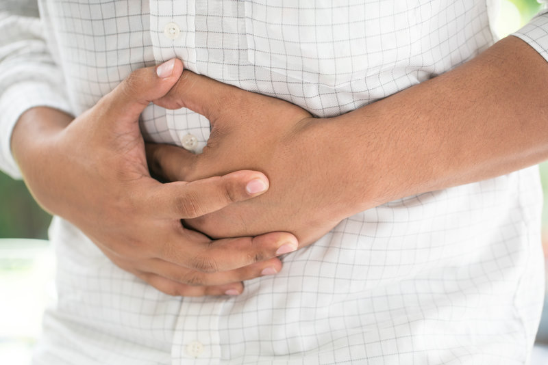 A man is putting his hands on his stomach