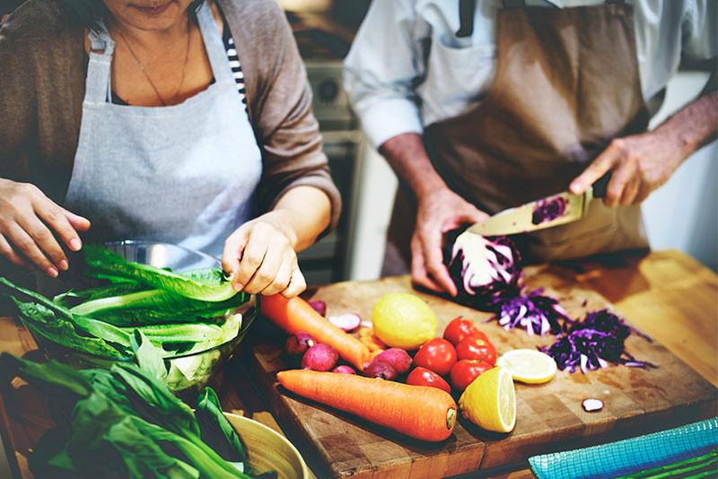 Ein Mann und eine Frau schneiden Gemüse auf einem Holzbrett