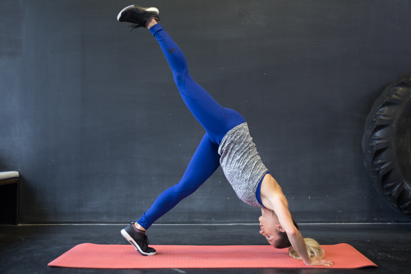 A woman is doing a single leg pipe push-up