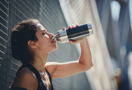 Woman drinking water after exercise