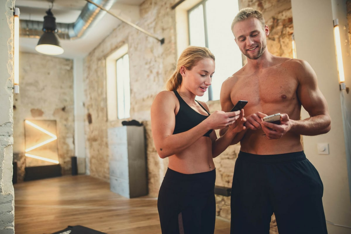 Man and woman looking at bodyweight exercises list for their workout