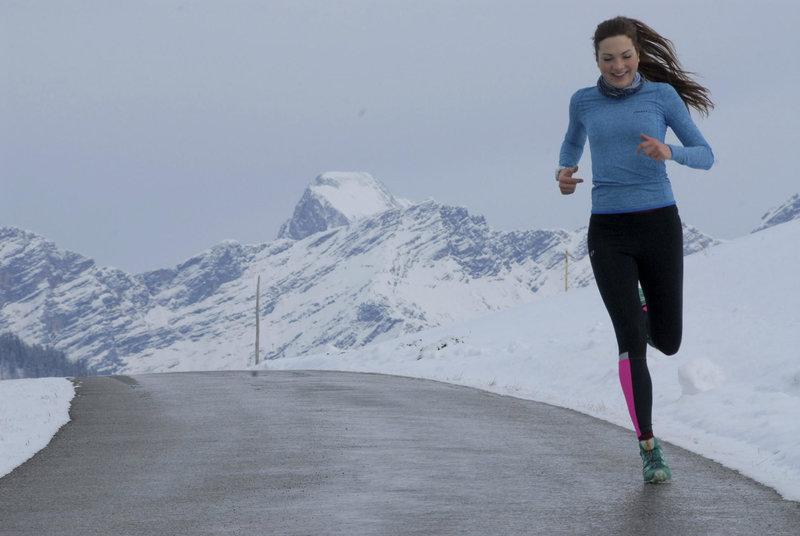 Junge Frau laeuft im Winter auf einer Bergstraße.